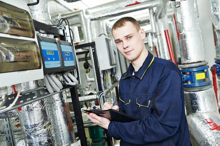 Ingeniero reparador o inspector del sistema de ingeniería de incendios o un sistema de calefacción con válvula de equipos en una sala de calderas Foto de archivo - 40274114