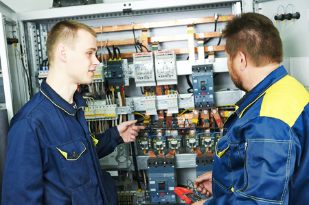 two electricians builder engineers discussing electrical components equipment near fuseboard distribution box photo