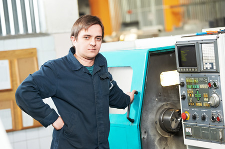 setup operator: industrial worker near cnc milling machine center at factory tool workshop Stock Photo