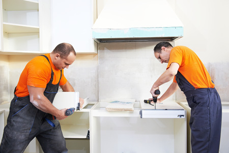 install: Craftsman kitchen carpenter workers at kitchen furniture set installation service work