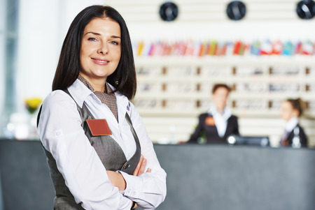 front desk: Happy female manager worker standing at hotel Stock Photo