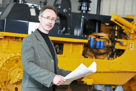 experienced: industrial engineer manager with technical drawing at heavy industry machinery assembling line for bulldozer production and manufacturing factory