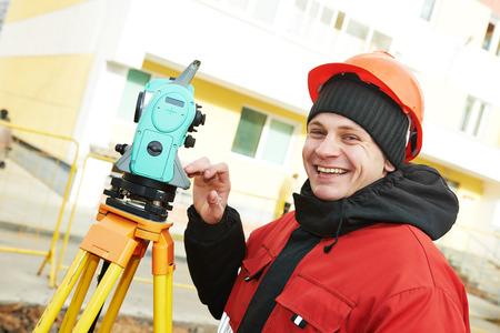 teodolito: Industria Topograf�a: sonriendo top�grafo positiva de trabajo con el equipo de tr�nsito teodolito en el sitio de construcci�n