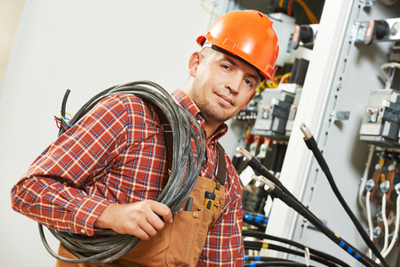 electrician engineer worker with cable in front of fuseboard equipment Stockfoto