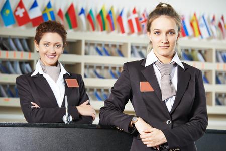uniformes: Feliz de pie femenino trabajador recepcionista en el mostrador del hotel