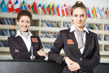 Happy female receptionist worker standing at hotel counter Standard-Bild