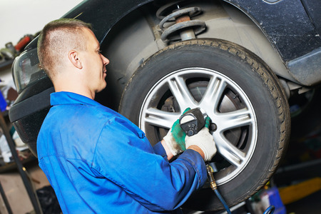 service station: car mechanic screwing or unscrewing car wheel of lifted automobile by pneumatic wrench at repair service station