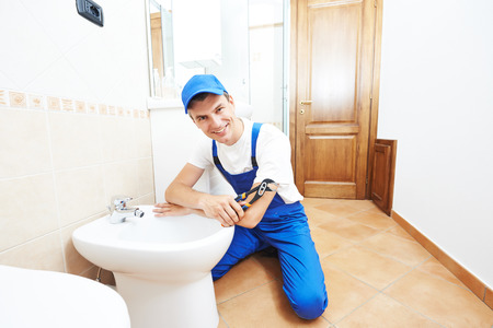 water sanitation: Smiling plumber worker with spanner at sanitary washbasin installation system Stock Photo