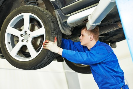 auto monteur: car mechanic inspecting suspension or brakes in car wheel of lifted automobile at repair service station