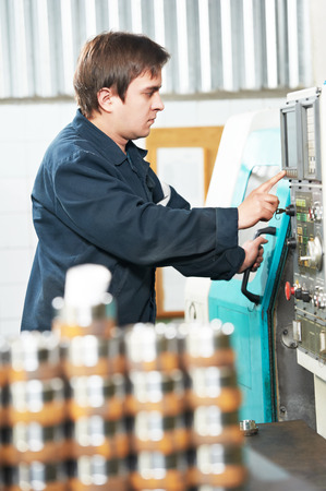 industrial worker near cnc milling machine center at factory tool workshop photo