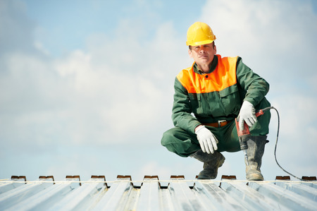 ouvrier: travailleur constructeur avec une perceuse à main à l'installation profil de toit métallique Banque d'images