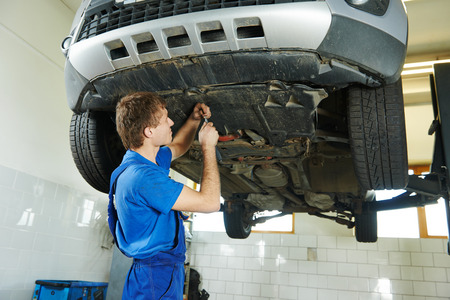 scheduled replacement: garage auto mechanic repairman assembling bottom car protection during car suspension repair of automobile maintenance at repair service station