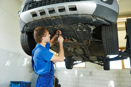 mantenimiento: reparador de garaje mec�nico de autom�viles montaje protecci�n de coche inferior durante la reparaci�n de la suspensi�n del coche del mantenimiento del autom�vil en la estaci�n de servicio de reparaci�n