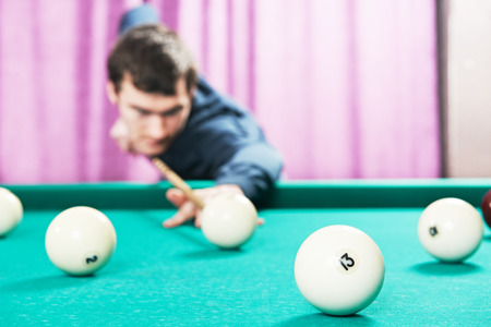 cue sports: Young player man with cue playing billiard or snooker game Stock Photo