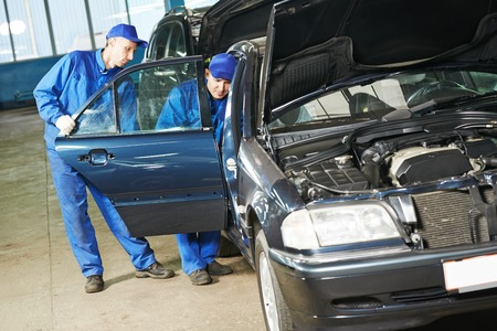 scheduled replacement: Two repairman mechanics matching automobile body side door on damaged car at repair service station Stock Photo