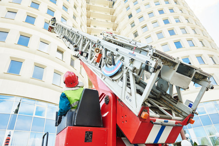 turnouts: fireman climbing a ladder with water hose for extinguish fire Stock Photo