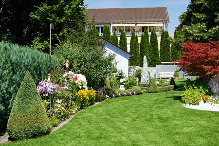 garden landscaping: landscape design. Garden with green grass and flowers near cottage