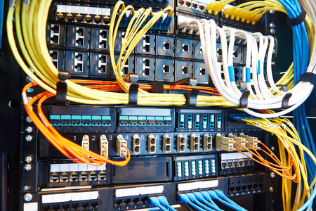 technology equipment with optical fibre cables connected to rack servers in room