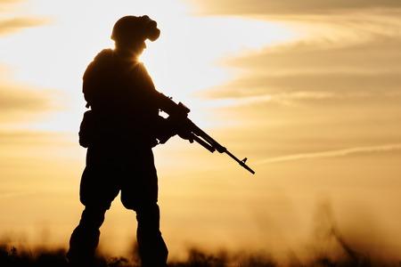 soldado: militar. silueta de soldado en uniforme con la ametralladora o fusil de asalto en el verano por la noche la puesta de sol