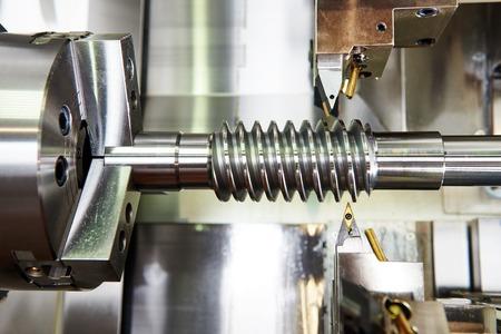 metalworking: metalworking  industry. cutting tool processing steel metal spiral pinion or worm screw shaft on lathe machine in workshop. Focus on tool.