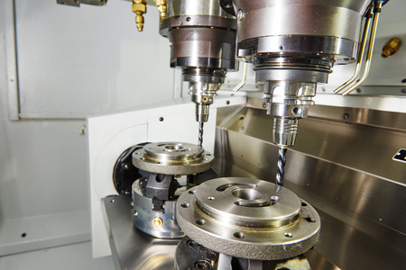 milling machine: Metalwork industry. Milling machine tool with two mills in chuck preparing to process metal detail at industrial manufacture factory Stock Photo