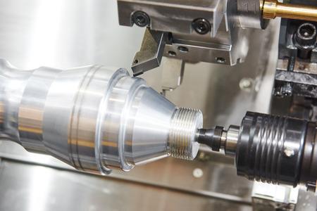 metalworking  industry: cutting steel metal shaft processing on lathe machine in workshop. Selective focus on tool Foto de archivo