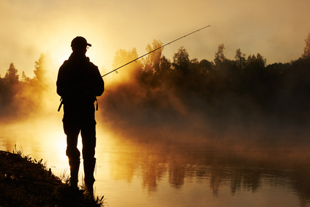 ponds: Fisher man fishing with spinning rod on a river bank at misty foggy sunrise