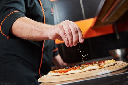 de hand van de chef-kok bakker in uniform toevoegen van kruiden in de pizza na pizza voorbereiding op restaurantkeuken Stockfoto