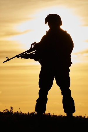 soldier: military. soldier silhouette in uniform with machine gun or assault rifle at summer evening sunset