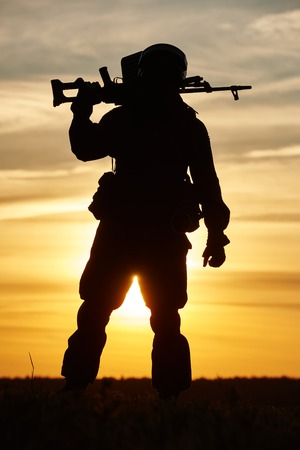 military. soldier silhouette in uniform with machine gun or assault rifle at summer evening sunset photo