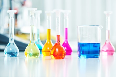 Pharmacy and chemistry theme. Test glass flask with solution in research laboratory. Shallow DOF. Focus on red bottle. Banque d'images