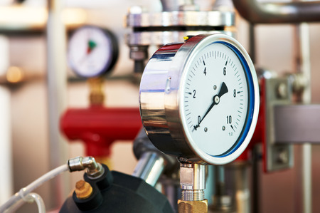 pharmaceutical plant: Closeup of manometer, pipes and faucet valves of heating system in a boiler room
