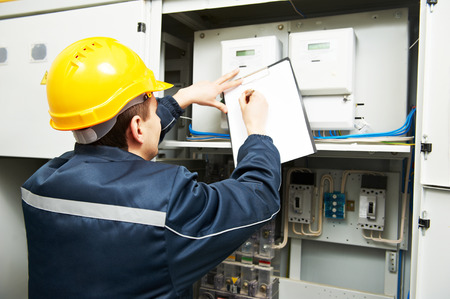 electrical safety: electrician builder engineer inspector checking data of equipment in fuse box
