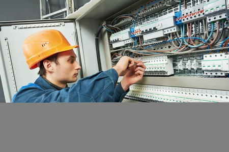 electrician with screwdriver tighten up switching electric actuator equipment in fuse box Stockfoto