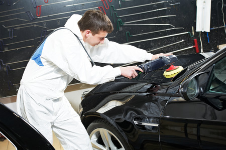 buffing: auto mechanic worker polishing car headlight at automobile repair and renew service station shop Stock Photo