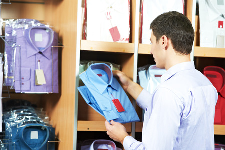 man choosing shirt during shopping at garments clothing shop photo