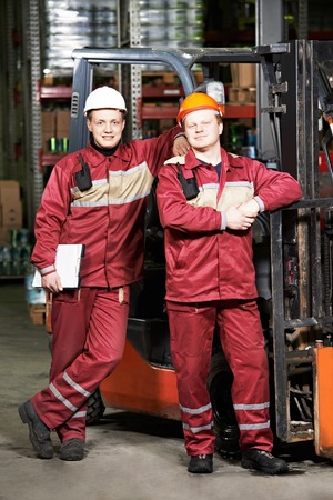 happy smiling warehouse workers in uniform in front of forklift stacker loader photo