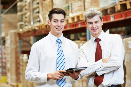 order delivery: two managers workers in warehouse with tablet computer Stock Photo