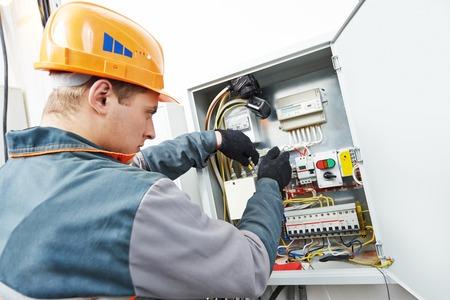 electricista: Adultos jóvenes de electricista ingeniero constructor de equipos atornillar la caja de fusibles