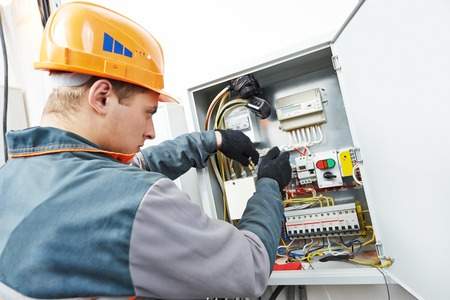 electrical contractor: Young adult electrician builder engineer screwing equipment in fuse box