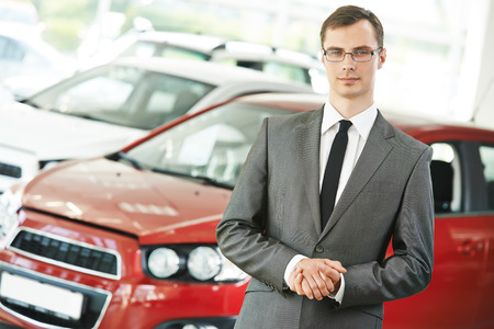 Portrait og salesperson or manager of car automobile dealer welcoming with open arms photo