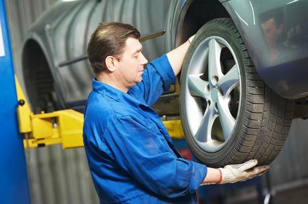 mecanico: atornillado mecánico de automóviles o la rueda del coche desatornillado de automóvil levantado por llave neumática en la estación de servicio de reparación