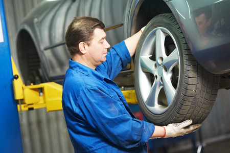 spare car: car mechanic screwing or unscrewing car wheel of lifted automobile by pneumatic wrench at repair service station