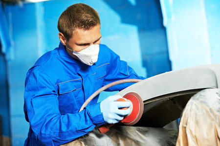 auto mechanic worker sanding polishing bumper car at automobile repair and renew service station shop by polishing grinding machine photo