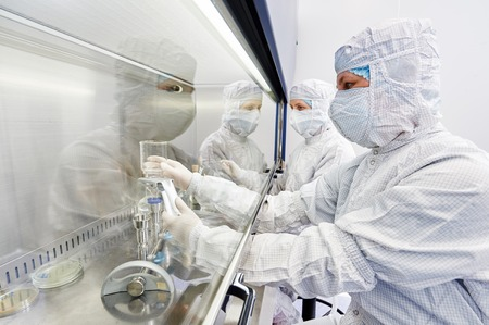 female science researchers in protective uniform and equipment works with dangerous hazard virus material at microbilogy laboratory