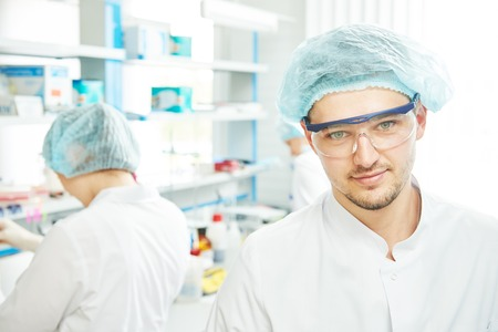 Portrait of young smiling male researcher in front of female researcher carrying out scientific test in chemistry laboratory photo