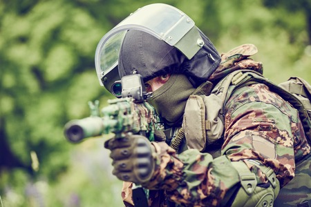 assault rifle: military. soldier in uniform targeting with assault rifle outdoors