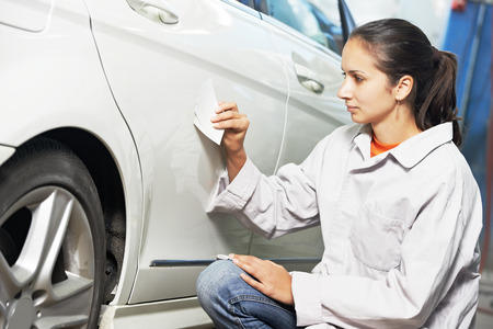 colourer: colourist woman matching paint of car element at automobile repair and renew service station with color example cards Stock Photo