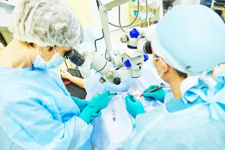 surgeon team in uniform in front of eye vision surgery operation room at medical clinic. selective focus - on operation area
