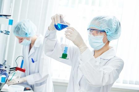 과학 실험실 작업. 플라스크에 파란색 액체 용액 작업 여성 과학 연구원 또는 의사 스톡 콘텐츠